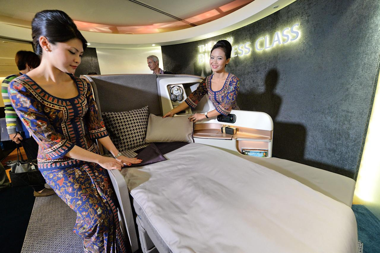 A Singapore Airlines (SIA) stewardesses stand next to a display of the new Singapore Airlines Business Class seat during their next generation cabin product launch in Singapore on July 9, 2013. SIA on July 9 unveiled new seats and other in-flight amenities as part of a sweeping upgrade of its cabins amid intensifying competition in the industry. AFP PHOTO / ROSLAN RAHMAN