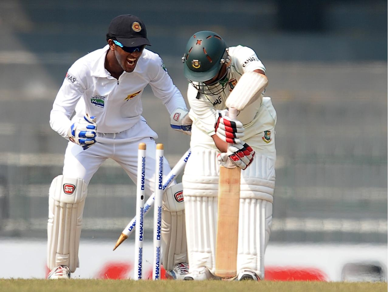 Bangladeshi cricketer Mohammad Ashraful (R) is dismissed by unseen Sri Lankan cricketer Rangana Herath as wicketkeeper Dinesh Chandimal (L) reacts during the third day of the second Test match between Sri Lanka and Bangladesh at the R. Premadasa Cricket Stadium in Colombo on March 18, 2013. AFP PHOTO/ LAKRUWAN WANNIARACHCHI