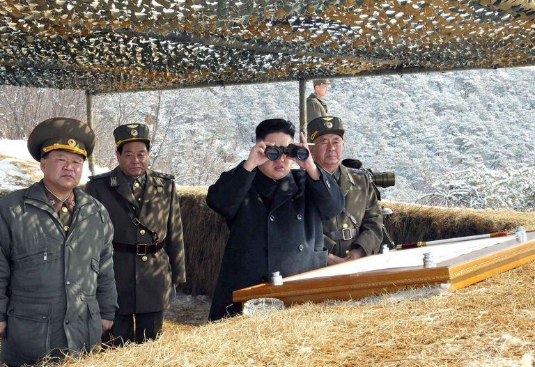 North Korean leader Kim Jong-Un use binoculars to inspect a live fire drill in North Korea, March 20, 2013