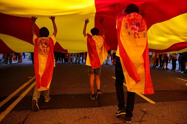 <p>Protesters draped in Spanish flags run under a giant Catalan flag during a pro-unity demonstration on Oct. 29, 2017 in Barcelona, Spain. (Photo: Jack Taylor/Getty Images) </p>