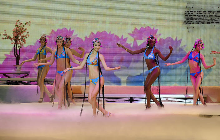 In this undated photo released by Miss Bikini International Committee on Thursday, Sept. 27, 2012, contestants wearing swimwears and traditional Chinese opera headpieces dance during an rehearsal for their up-coming bikini competition in Beijing. A stage performance by bikini-clad women wearing headpieces styled after traditional Peking Opera has sparked debate in China after photos were made public this week, highlighting divided views on how to preserve the country's traditions. (AP Photo/Miss Bikini International Committee) EDITORIAL USE ONLY, NO SALES