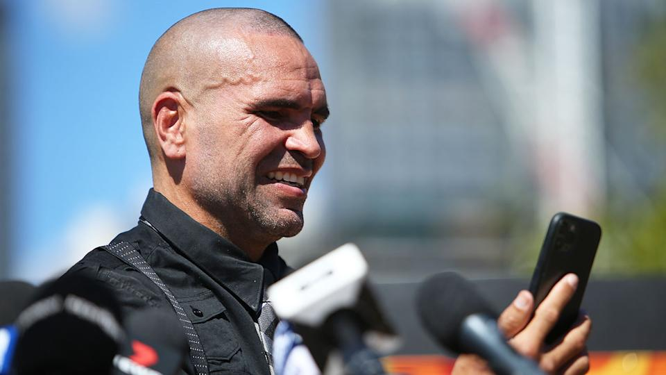 Seen here, Anthony Mundine reacts to a call from surfing legend Kelly Slater.