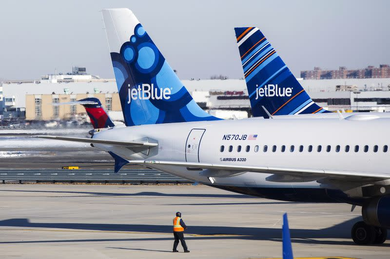 File photo of an airport worker leading JetBlue planes onto the tarmac of the John F. Kennedy International Airport in New York