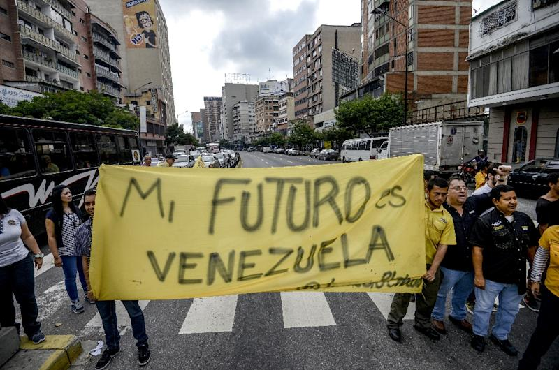 "Venezuelan opposition activists march along a street of Caracas on March 31, 2017 chanting slogans against the government of President Nicolas Maduro and deploying a banner that reads ""My Future Is Venezuela"" (AFP Photo/Juan Barreto)"