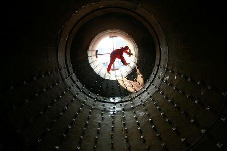 A worker checks steel pipes at an oil field preparing for oil and gas exploitation in Yilong
