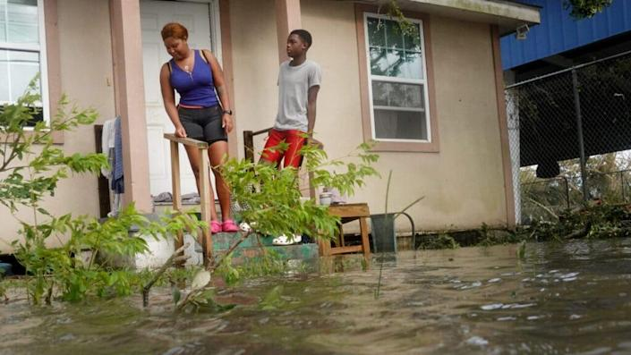 Michelle Washington and her son Kendrick check out damage to their home in the aftermath of Hurricane Ida on August 30, 2021 in Kenner, Louisiana. Ida made landfall yesterday as a category 4 storm southwest of New Orleans. (Photo by Scott Olson/Getty Images)
