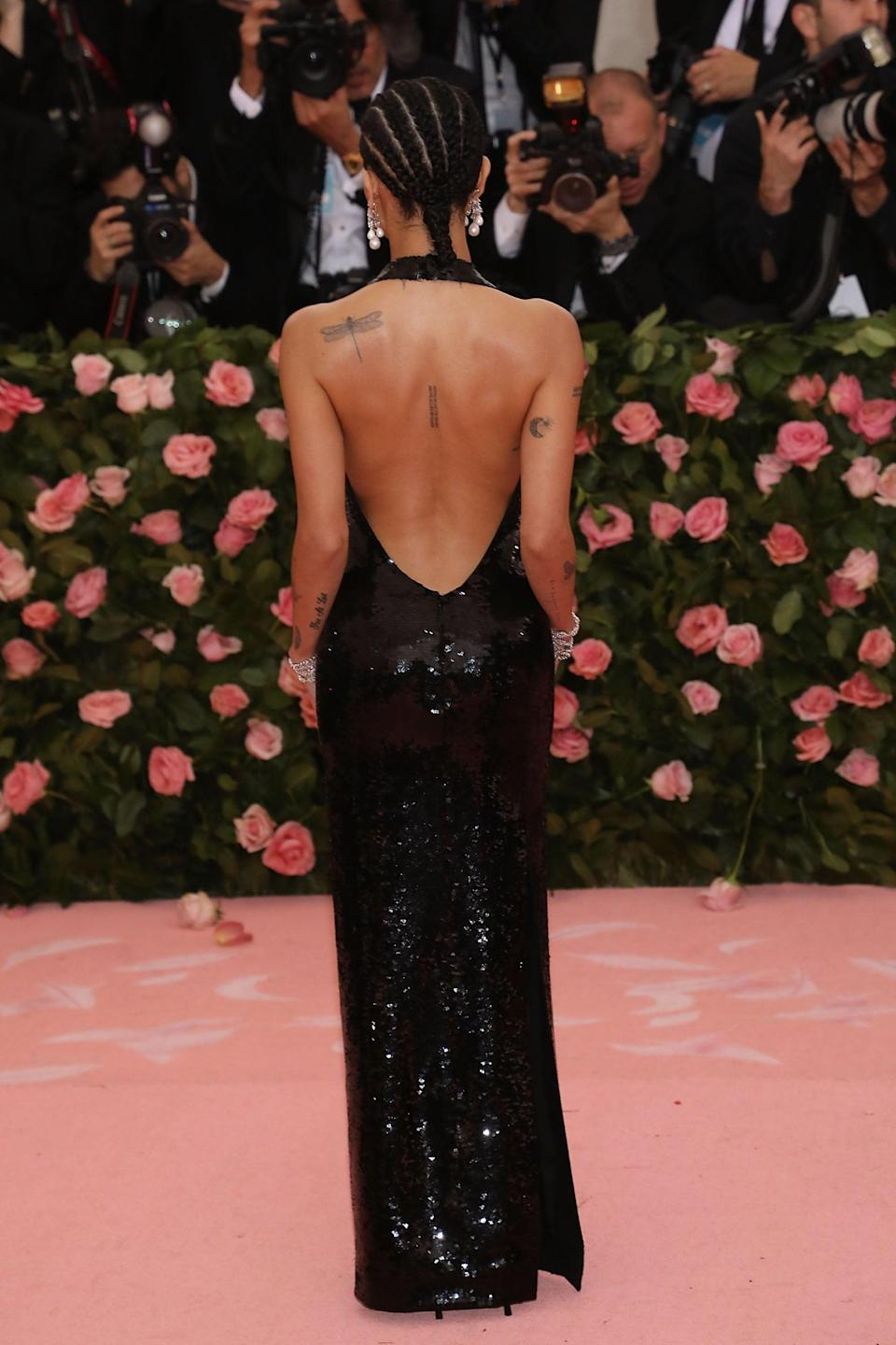 """<p>On the upper left corner of her back shoulder is a detailed dragonfly. After learning that her previous Arabic script tattoo was grammatically incorrect (it was supposed to read """"let love rule""""), Kravitz completed laser removal then had Dr. Woo cover up the area with the whimsical piece. </p> <p>Kravitz also has two lines of script on her spine in black ink, however it is difficult to see in photos and she has not disclosed the tattoo's meaning.</p>"""