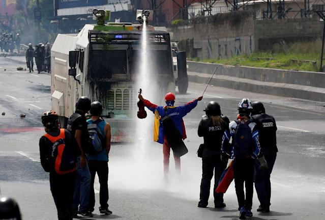 <p>A demonstrator stands in front of a riot security forces vehicle during a rally against President Nicolas Maduro in Caracas, Venezuela, May 24, 2017. (Photo: Carlos Garcia Rawlins/Reuters) </p>