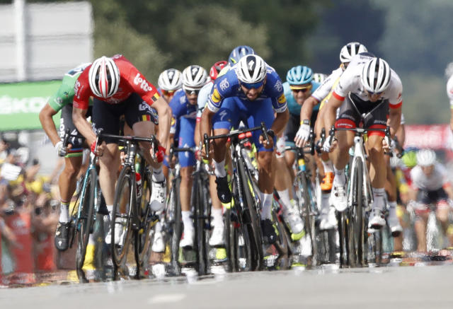 Colombia's Fernando Gaviria, center, sprints to win the fourth stage of the Tour de France cycling race over 195 kilometers (121 miles) with start in La Baule and finish in Sarzeau, France, Tuesday, July 10, 2018. (AP Photo/Christophe Ena )