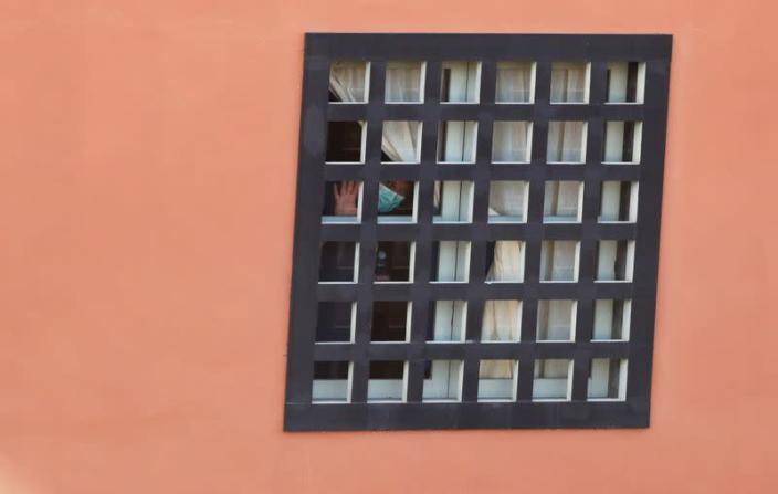 A tourist looks through the hotel window H10 Costa Adeje Palace, which is on lockdown after novel coronavirus has been confirmed in Adeje