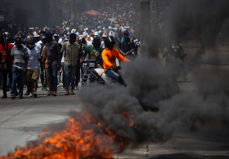 Demonstrators march near a burning road block during a protest against the government of President Jovenel Moise, in Port-au-Prince