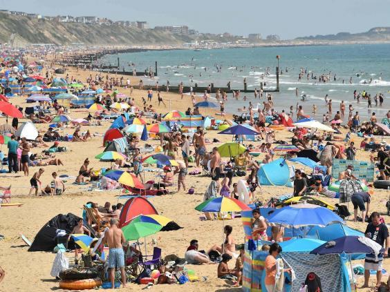 Beachgoers enjoy the sunshine as they sunbathe and play in the sea on Bournemouth beach in Bournemouth (AFP via Getty Images)