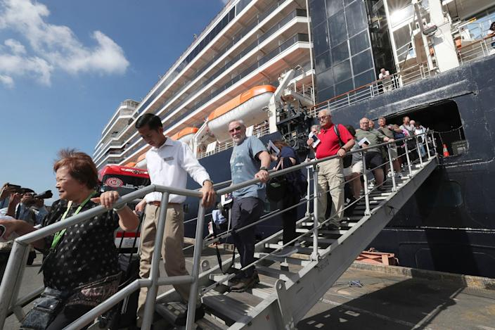 Passengers of the MS Westerdam disembarking at the port of Sihanoukville on Saturday.