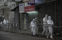 Government workers wearing personal protective equipment walk at the closed area in Jordan district, in Hong Kong, Sunday, Jan. 24, 2021. Thousands of Hong Kong residents were locked down Saturday in an unprecedented move to contain a worsening outbreak in the city, authorities said. (AP Photo/Vincent Yu)