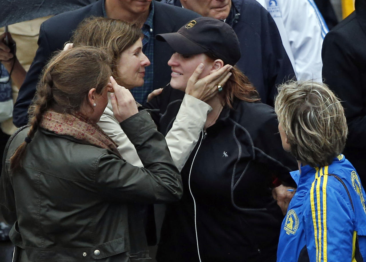 2013 Boston Marathon bombing survivor Erika Brannock, in hat, a pre-school teacher from the Baltimore area, is embraced as she walks across the Marathon finish line after a remembrance ceremony on Boylston Street in Boston, Tuesday, April 15, 2014. (AP Photo/Elise Amendola)