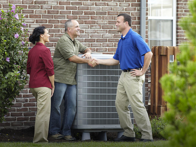Two people shaking hands in front of an outside air conditioner, with third person watching