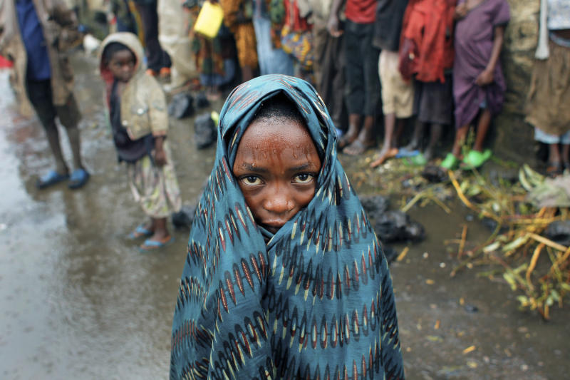 A Congolese child waits with others in the rain for aid to be distributed in Kibati, north of Goma, eastern Congo, Wednesday Aug. 8, 2012. Drenching rain punctuated by frightening bursts of thunder and forked lightning add to the misery of some of the 280,000 refugees from Congo's eastern rebellion, whose plight is highlighted by a visit from the U.N. humanitarian chief Baroness Valerie Amos. (Photo: Jerome Delay/AP)