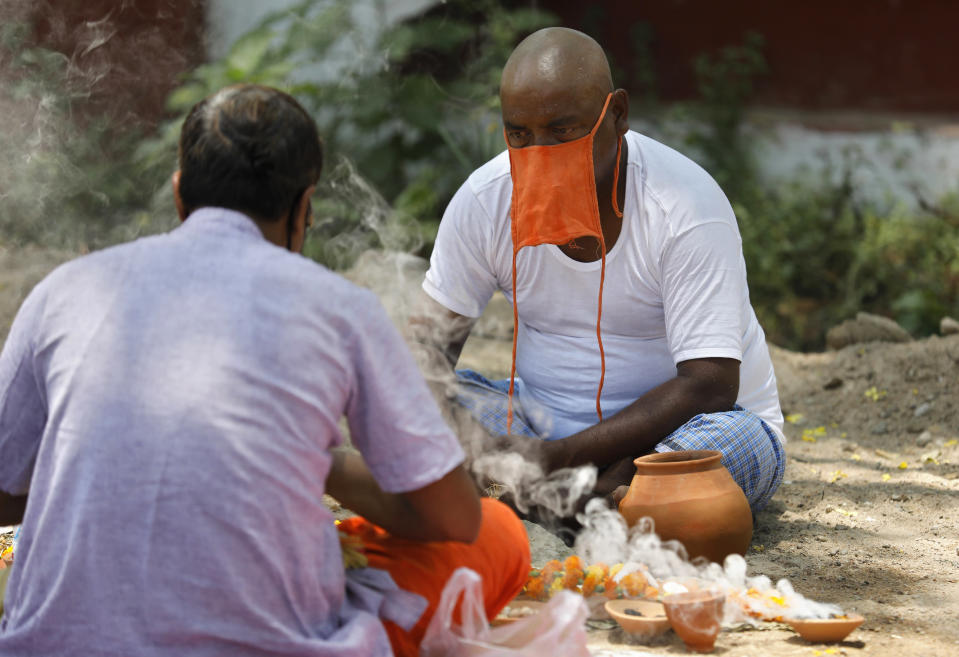 Family member, right, of a person who died of COVID-19 performs Hindu rituals in Prayagraj, India, Saturday, May 15, 2021. India's Prime Minister Narendra Modi on Friday warned people to take extra precautions as the virus was spreading fast in rural areas. (AP Photo/Rajesh Kumar Singh)