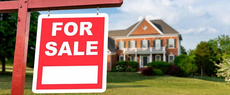 For Sale realtor sign in front of large brick single family house in expansive grass yard for real estate opportunity