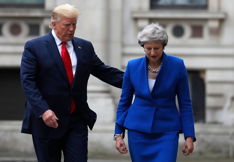 Britain's Prime Minister Theresa May and President Donald Trump walk through the Quadrangle of the Foreign Office for a joint press conference in central London, June 4, 2019. (Photo: Frank Augstein/AP)