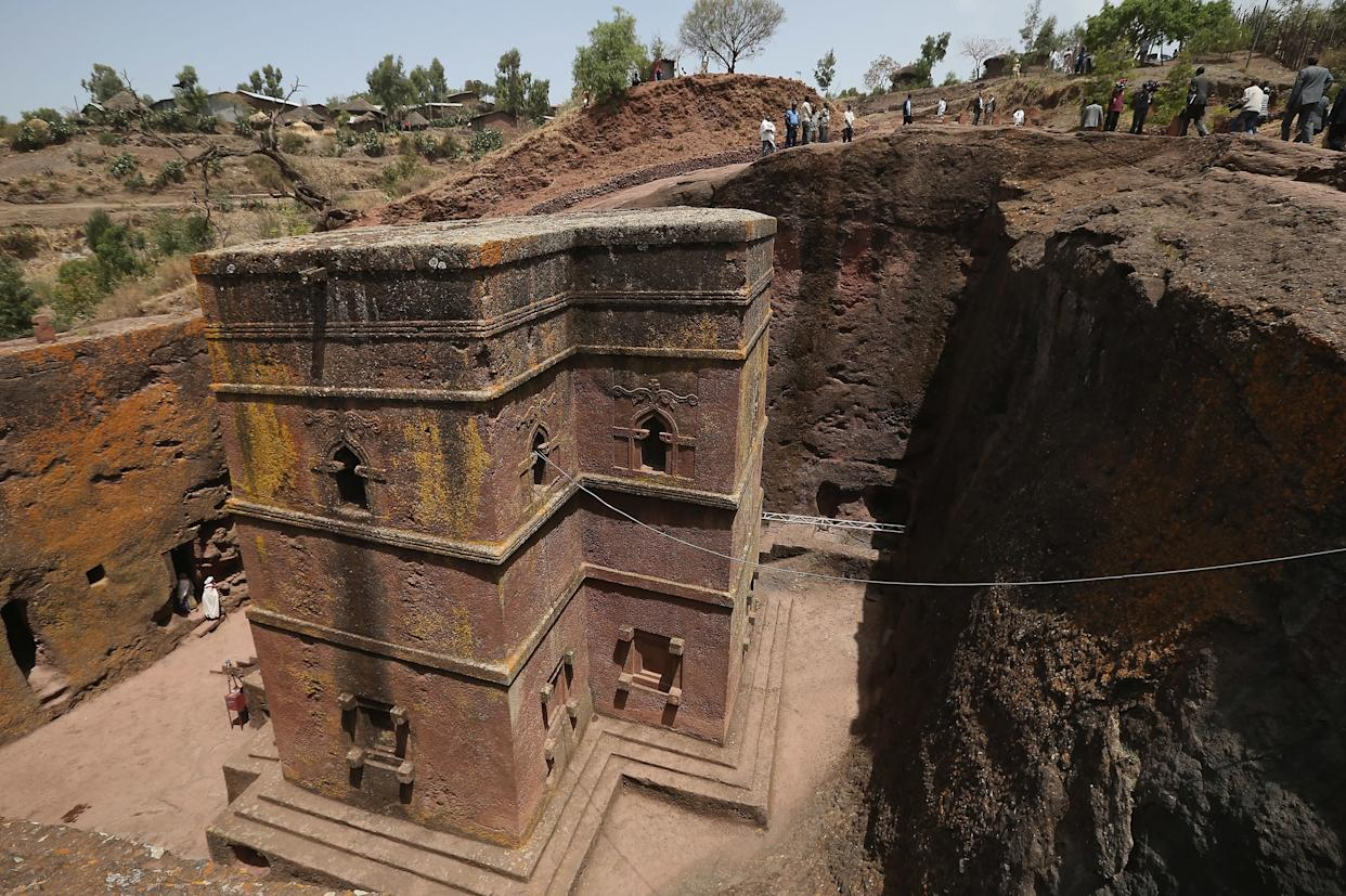 Visitors walk past Bete Giyorgis, also called St. George's Church, on March 19, 2013, in Lalibela, Ethiopia. Lalibela is among Ethiopia's holiest of cities and is distinguished by its 11 churches hewn into solid rock that date back to the 12th century. Construction of the churches was begun by Ethiopian Emperor Gebre Mesqel Lalibela, who sought to create an alternative pilgrimage site after the Muslim occupation of Jerusalem. Lalibela was the capital of Ethiopia until the 13th century.