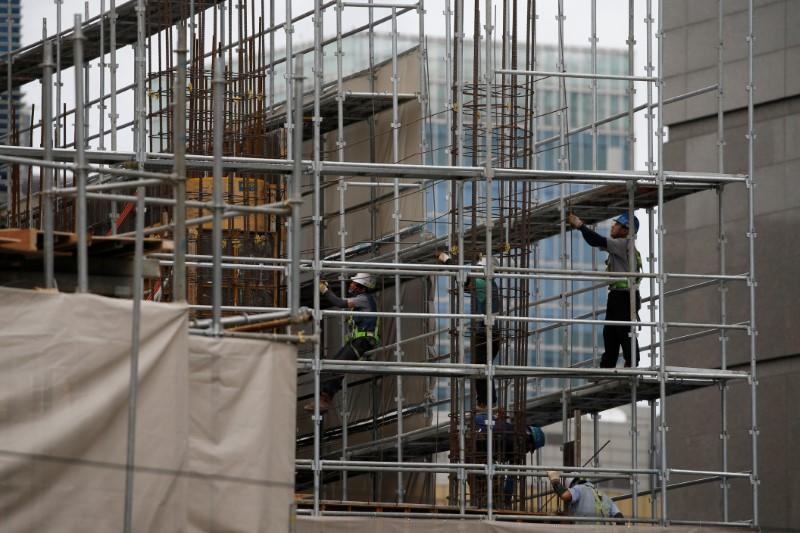 Workers labour on steel frames at a construction site in central Seoul