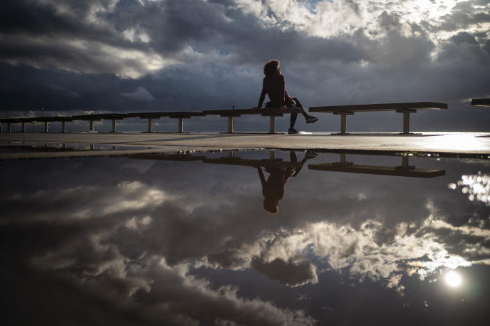 A woman sits in front of the sea after a storm in Barcelona, Spain, Wednesday Oct. 14, 2020. Various regions in Spain, including northern Navarra and northeastern Catalonia, are either planning or implementing fresh restrictions against the spread of the new coronavirus. (AP Photo/Emilio Morenatti)