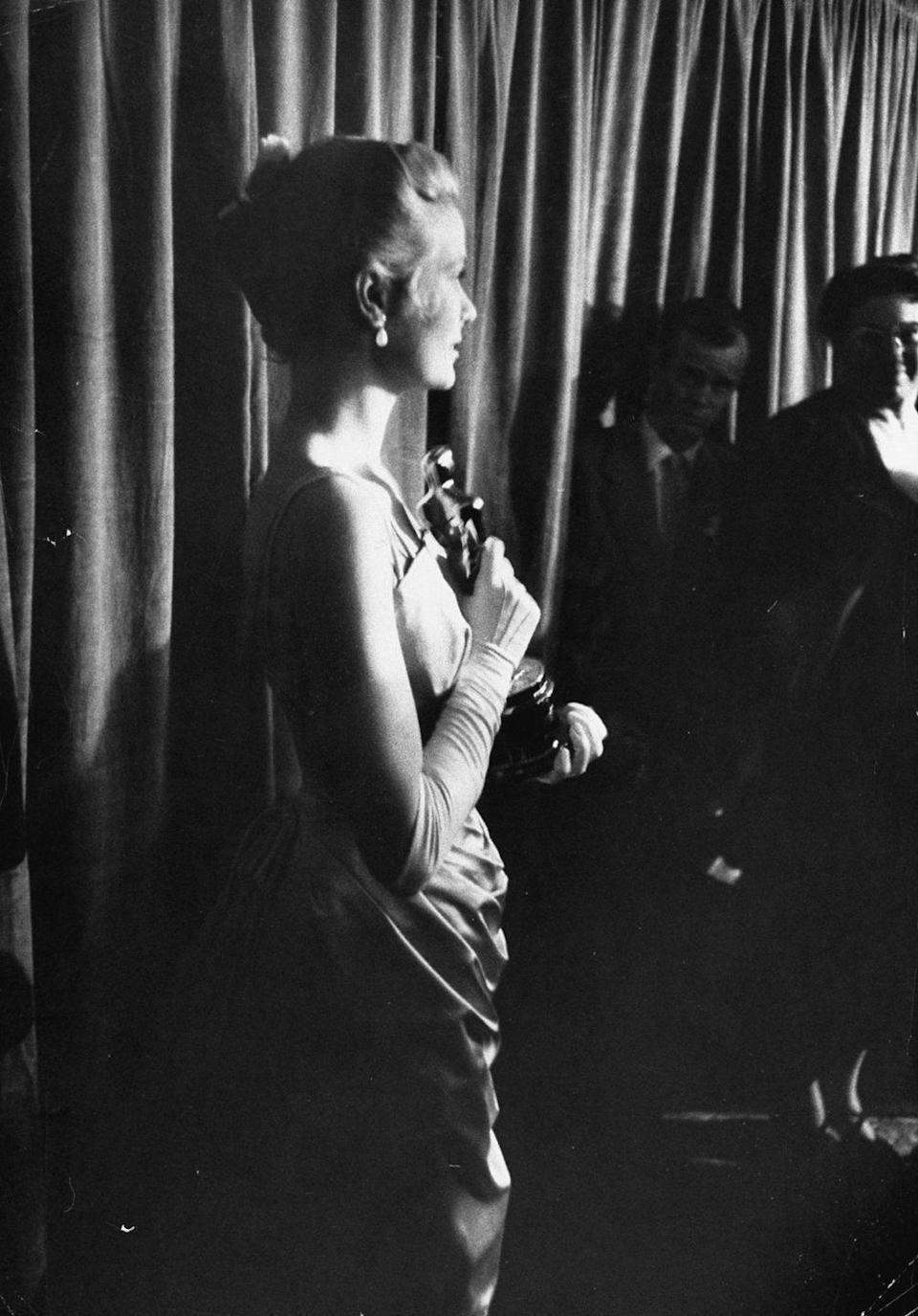 <p>Kelly smiles for the cameras backstage at the Academy Awards after winning her Oscar on March 30, 1955. Despite a prior nomination, this was Kelly's only recognition from the Academy.</p>