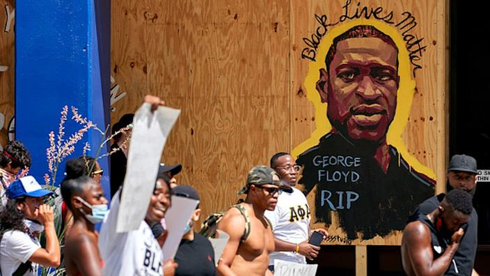 Demonstrators march past a mural remembering George Floyd in Texas