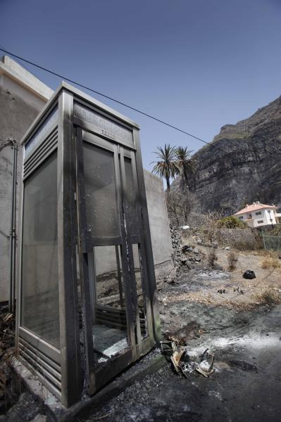 A burned-out public telephone box stands in a burned valley in Barranco de Guada on the Canary island of La Gomera, Spain Tuesday Aug. 14, 2012. Spanish authorities said Morocco sent two water-carrying planes to help in the battle to extinguish the wildfires that have torched some 3,000 hectares of land on the Canary Island of La Gomera, including areas of a UNESCO World Heritage Site national park. (AP Photo/Yaiza Mesa)