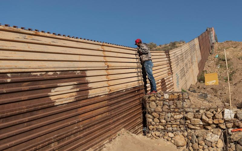 A migrant from Honduras looks from the border fence into the US side to San Diego, California - AP