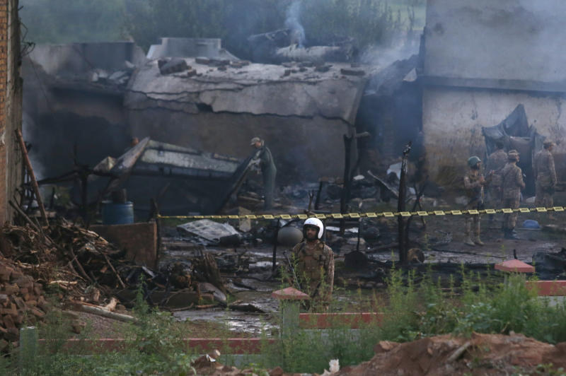 Pakistan army officials examine the site of a plane crash in Rawalpindi, Pakistan, Tuesday, July 30, 2019. A small Pakistani military plane crashed into a residential area near the garrison city of Rawalpindi before dawn, killing some people, officials said. (AP Photo/Anjum Naveed)