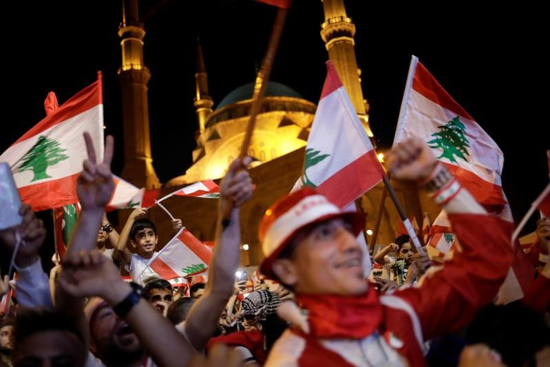 Protesters gesture as they wave flags at a demonstration during ongoing anti-government protests in Beirut