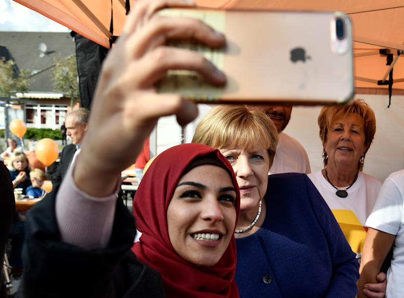 A Syrian refugee poses for a selfie with Angela Merkel during a campaign stop a week before the election. (JOHN MACDOUGALL via Getty Images)