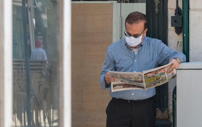 A man reading a newspaper in Lisbon, Portugal, on May 20.