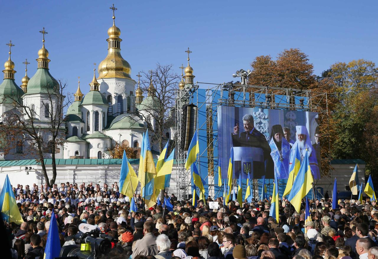 """People listen to Ukraine's President Petro Poroshenko as they gather to participate in a mass prayer to express gratitude to Istanbul-based Ecumenical Patriarchate for granting approval to establish the country's independent, or """"autocephalous"""", church in Kiev, Ukraine October 14, 2018. REUTERS/Gleb Garanich"""