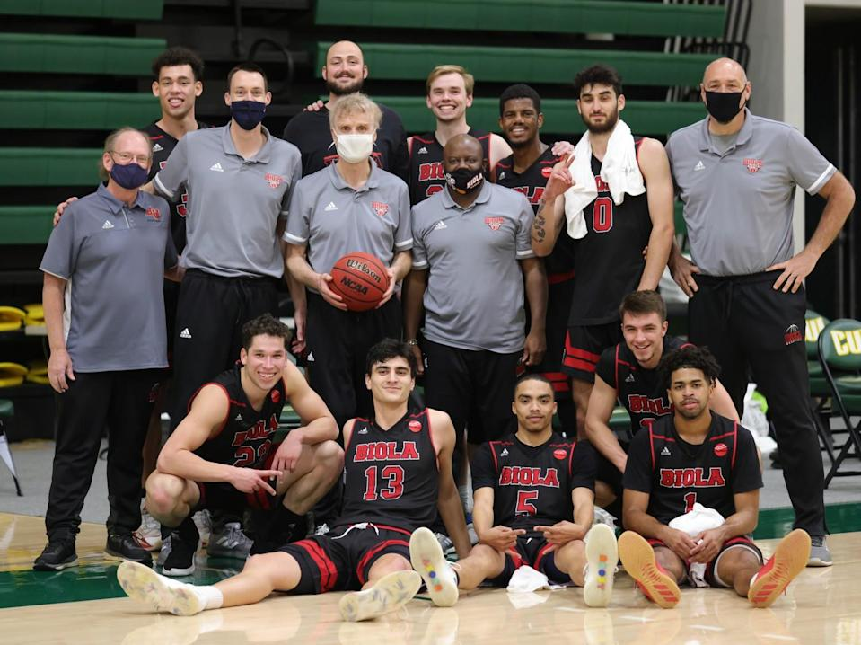 Biola University coach Dave Holmquist celebrates with his players and assistants following his 1,000th career win on Feb. 27.