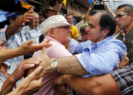 Colombian presidential candidate Oscar Ivan Zuluaga embraces a supporter as he greets the crowd during a closing campaign rally in Villeta