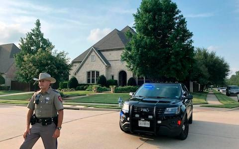 A police officer stands outside a home in Allen, Texas, believed to be associated with a mass shooting  - Credit: AP