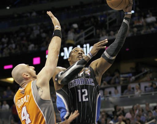 Orlando Magic center Dwight Howard (12) shoots around Phoenix Suns center Marcin Gortat (4), of Poland, during the first half of an NBA basketball game Wednesday, March. 21, 2012, in Orlando Fla. (AP Photo/Reinhold Matay)