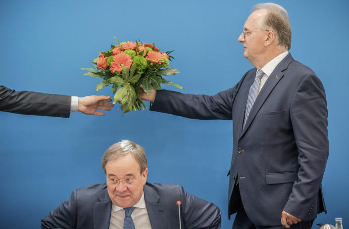 07 June 2021, Berlin: Reiner Haseloff, Minister President of Saxony-Anhalt, hands over the bouquet of flowers he received from the CDU Federal Chairman and Minister President of North Rhine-Westphalia, Armin Laschet (front), to a person before the start of the CDU Federal Executive Committee meeting in Berlin, Germany, Monday, June 7, 2021. The top bodies are discussing the results after the state elections in Saxony-Anhalt. (Michael Kappeler/Pool via AP)