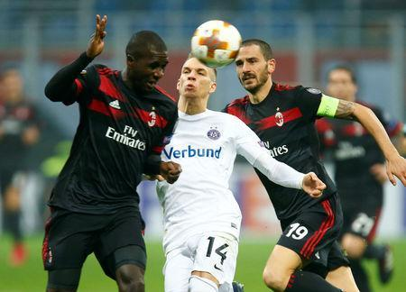 AC Milan's Cristian Zapata and Leonardo Bonucci in action with Austria Vienna's Christoph Monschein. REUTERS/Alessandro Garofalo