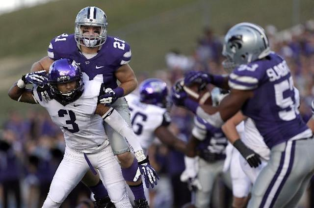 Kansas State linebacker Blake Slaughter intercepts a ball intended for TCU wide receiver Brandon Carter (3) as Carter is defended by Kansas State linebacker Jonathan Truman (21) during the first half of an NCAA college football game Saturday, Nov. 16, 2013, in Manhattan, Kan. (AP Photo/Charlie Riedel)