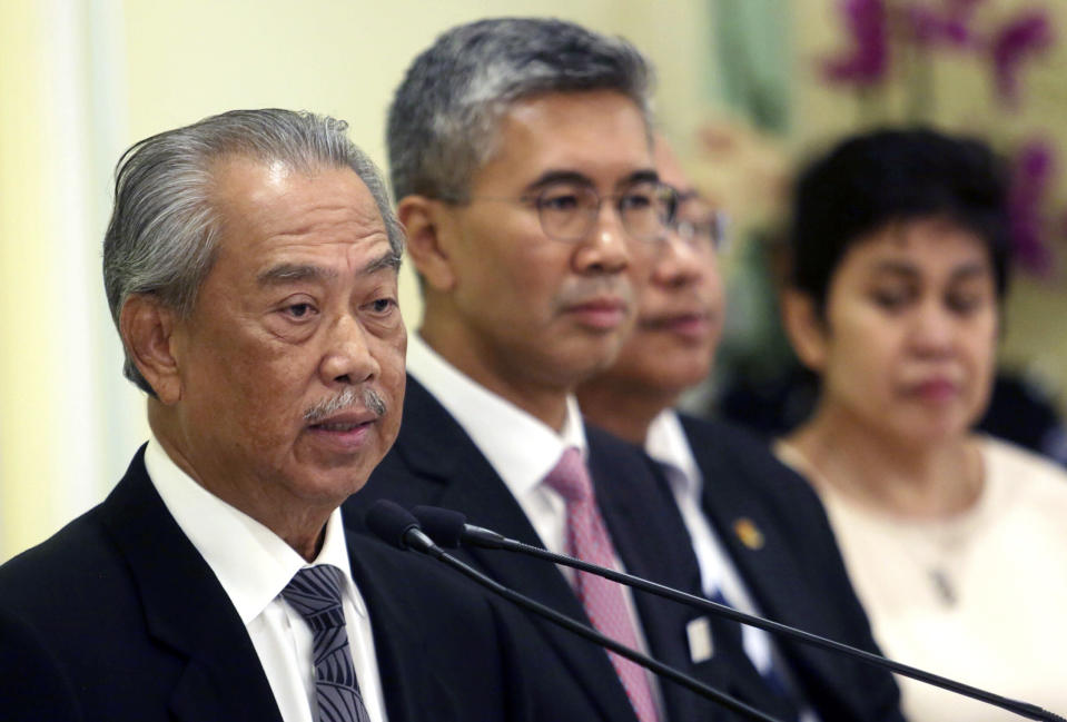 Malaysian Prime Minister Muhyiddin Yassin, left, speaks during a press conference at prime minister's office in Putrajaya, Malaysia, Monday, March 16, 2020. From March 18 till March 31, all business and religious activities in the country will be suspended to curb the spread of the coronavirus, said Prime Minister Muhyiddin Yassin. For most people, the new coronavirus causes only mild or moderate symptoms. For some it can cause more severe illness, especially in older adults and people with existing health problems. (AP Photo)