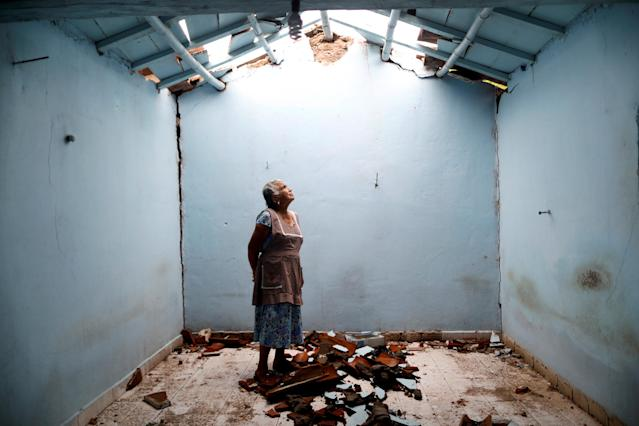 """<p>Tomasa Mozo, 69, a housewife, looks up at the roof as she poses for a portrait inside the ruins of her house after an earthquake in San Jose Platanar, at the epicentre zone, Mexico, September 28, 2017. The house was badly damaged but with the help of her family Mozo rescued some furniture. She lives in another room of her house and hopes to repair the damage as soon as possible. """"I'm afraid to go out, I can not sleep,"""" Mozo said. (Photo: Edgard Garrido/Reuters) </p>"""