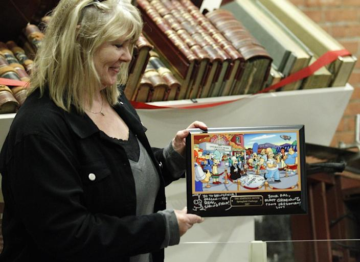 """Debra Gruell, Executive Director Springfield Museum, holds a plaque that was given by """"The Simpsons"""" creator Matt Groening at the Springfield Museum Tuesday, April 10, 2012, in Springfield, Ore. One of the best-kept secrets in television history has been revealed, with """"The Simpsons"""" creator Matt Groening pointing to Springfield, Ore., as the inspiration for the animated hometown of Homer and his dysfunctional family. Groening told Smithsonian magazine, published online Tuesday, that he was inspired by the television show """"Father Knows Best,"""" which took place in a place called Springfield. Springfield, Ore., is 100 miles south of Groening's hometown of Portland. (AP Photo/Rick Bowmer)"""