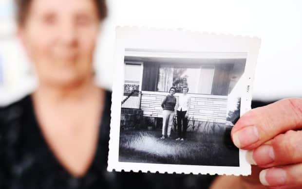 Ryczak holds a photograph of when she, pictured left, and Wallace first met in 1967, 17 years after their friendship started.