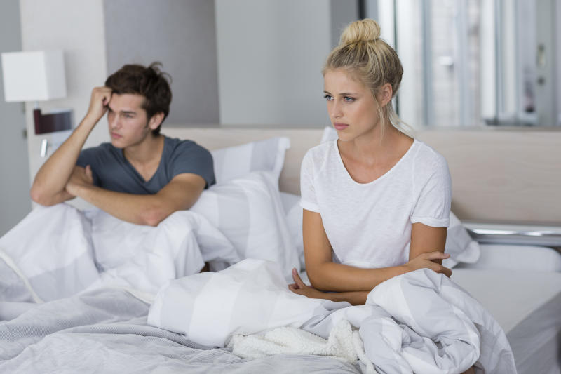 Young couple sitting on the bed with relationship difficulties
