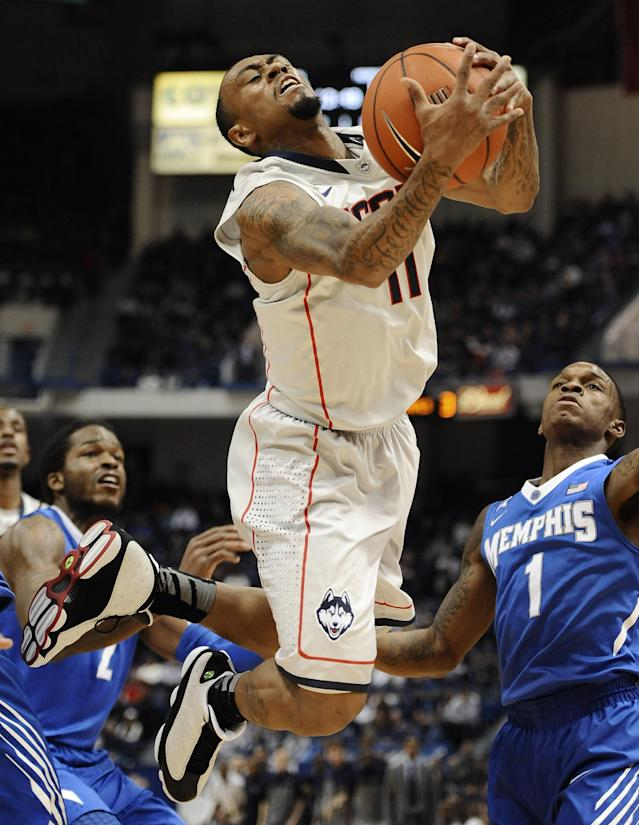 Connecticut's Ryan Boatright is fouled and flies out-of-bounds as Memphis' Shaq Goodwin, left, and Joe Jackson, right, defend during the first half of an NCAA college basketball game, Saturday, Feb. 15, 2014, in Hartford, Conn. (AP Photo/Jessica Hill)