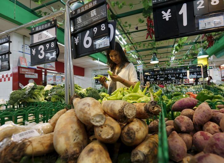 A woman chooses vegetables at a supermarket in Beijing